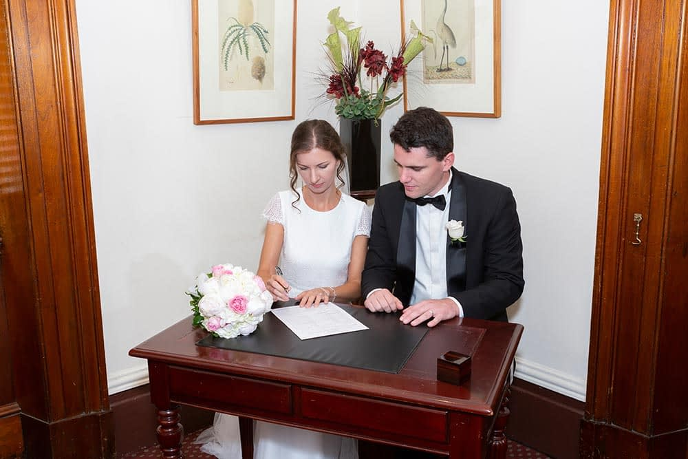 bride and groom signing wedding certificate at wedding ceremony