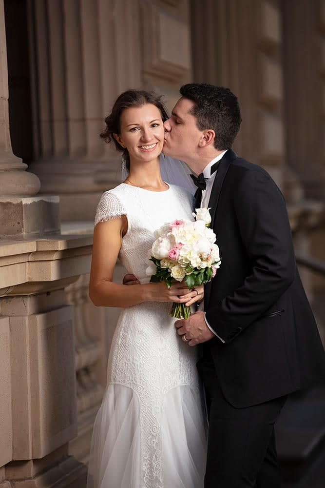 a groom kiss his bride at old treasury building