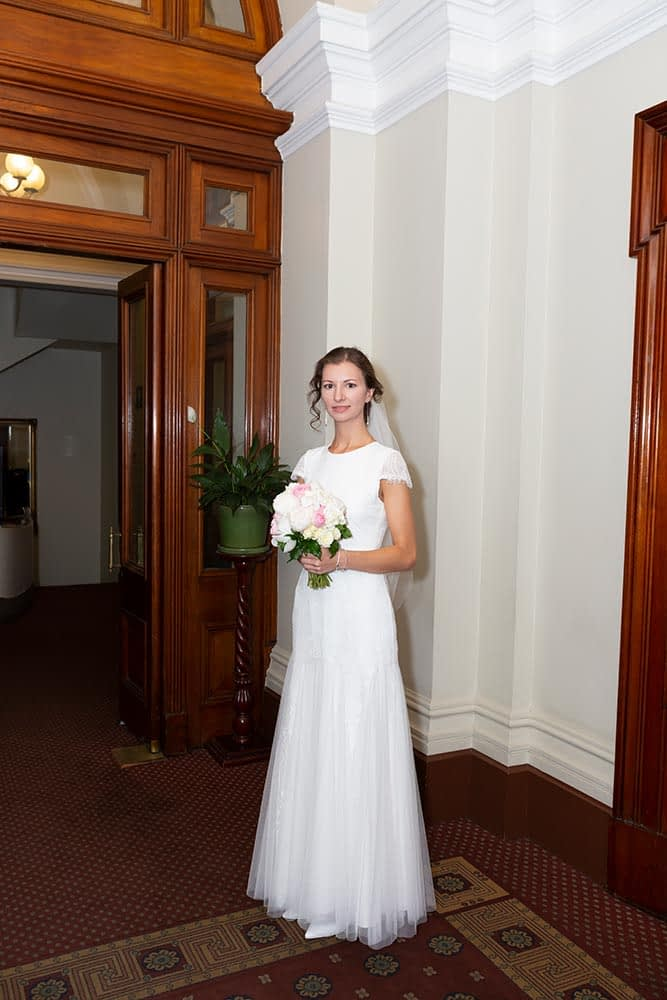 bride holding flowers inside old treasury building