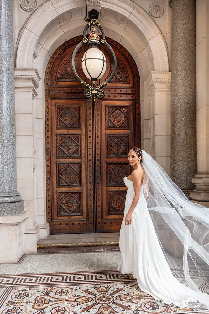 Bride walking toward the parliament house door.