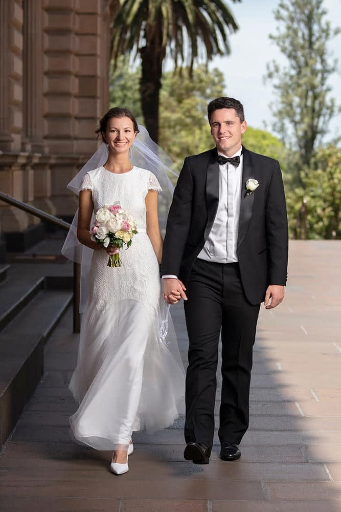 Bride and groom walking and holding hand at old treasury building